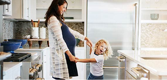 A pregnant mother and her son dancing in the kitchen.