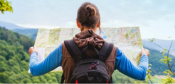 A woman hiking looking at a map.